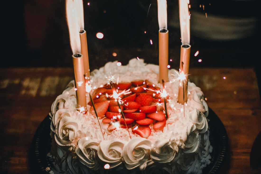 lighted candles on white icing covered cake